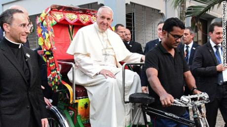 Pope Francis takes a ride in a rickshaw during the second day of his visit to Bangladesh, in Dhaka on December 1, 2017.