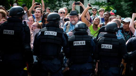 Riot police hold back counterprotesters as Ku Klux Klan members leave last year's Charlottesville rally.