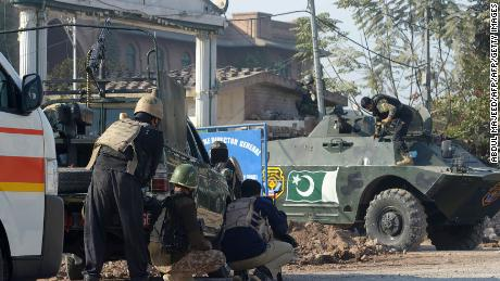 Pakistani security takes position Friday after an attack on the Agricultural Training Institute in Peshawar.