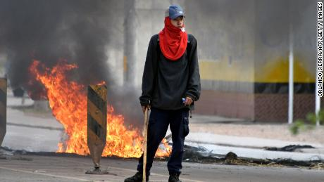 A supporters of Honduran presidential candidate for the Opposition Alliance against the Dictatorship coalition, Salvador Nasralla, stands amid the street during protests demanding for the final results of the weekend's presidential election, in Tegucigalpa, on December 1, 2017.   Honduran President Juan Orlando Hernandez edged closer Thursday to winning a tense election as police battled opposition protestors and rival Salvador Nasralla said he will not recognize the result. Under a haze of tear gas in the capital, anti-riot police fought running battles with several hundred Nasralla supporters, some armed with sticks. The election in this poor, gang-plagued country has turned into a drawn-out showdown between Nasralla, 64, and Hernandez, 49, who is going for four more years in office despite a constitutional limit of just one term.   / AFP PHOTO / ORLANDO SIERRA        (Photo credit should read ORLANDO SIERRA/AFP/Getty Images)