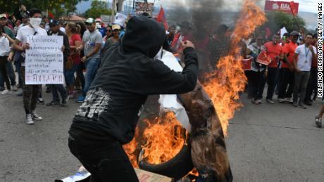 Supporters of the presidential candidate for Honduras' Opposition Alliance against the Dictatorship, Salvador Nasralla, burn campaign posters of his rival, President Juan Orlando Hernandez, during a demonstration claiming that Nasralla won the November 26 elections, near the Supreme Electoral Tribunal in Tegucigalpa on December 3, 2017.  Honduras aims to resume the vote count to define the winner of the November 26 elections between President Juan Orlando Hernandez and the opposition candidate Salvador Nasralla. One young woman was killed and at least 12 civilians have been wounded during violent clashes sparked by Nasralla's call for his supporters to take to the streets.