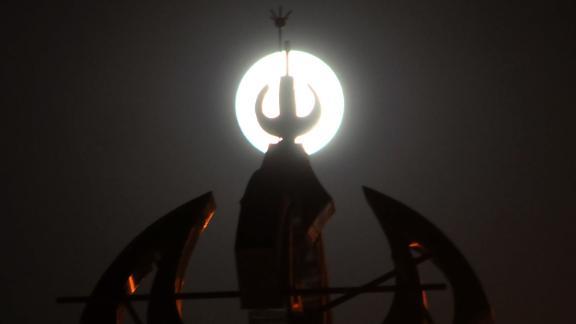 The supermoon is seen behind a minaret in Rawalpindi, Pakistan.