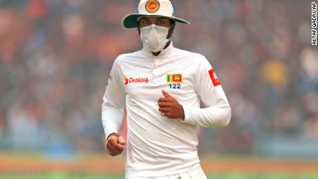 Captain of Sri Lanka's cricket team, Dinesh Chandimal wears an anti-pollution mask during the cricket match in New Delhi on Sunday, December 3.