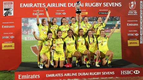 Members of Australia's women's national rugby sevens team lift the trophy as they celebrate their victory, after defeating the United States in the Dubai Sevens Cup final on December 1, 2017. / AFP PHOTO / KARIM SAHIB        (Photo credit should read KARIM SAHIB/AFP/Getty Images)