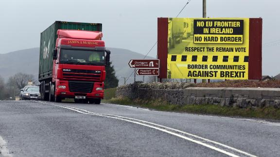 Traffic crosses the border into Northern Ireland from the Irish Republic next to a poster protesting against a hard brexit near Dundalk on January 30, 2017.