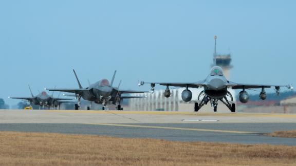 A US Air Force F-16 and four F-35A fighter jets taxi toward the end of the runway during exercise Vigilant Ace at Kunsan Air Base in South Korea.