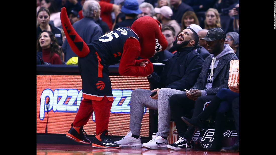 The Toronto Raptors' mascot jokes with rapper Drake during an NBA game on Friday, December 1.