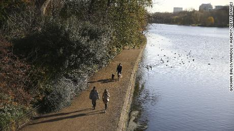 People take a walk in Hyde Park during the last days of autumn in October.