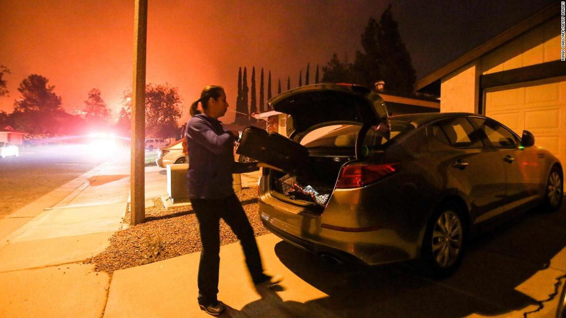 A woman evacuates her home as the fire burns in Santa Paula on December 5.