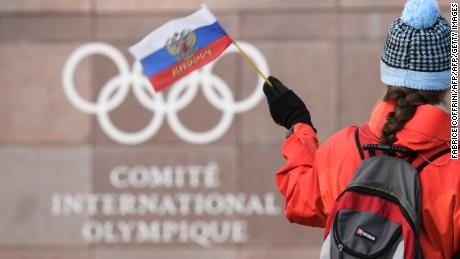 A supporter waves a Russian flag in front of the logo of the International Olympic Committee (IOC) at their headquarters on December 5, 2017 in Pully near Lausanne. The International Olympic Committee opened a high-stakes summit on December 5 on whether to bar Russia from the Winter Olympics over allegations its medal haul at the 2014 Sochi Games was fuelled by state-sponsored doping. / AFP PHOTO / Fabrice COFFRINI        (Photo credit should read FABRICE COFFRINI/AFP/Getty Images)