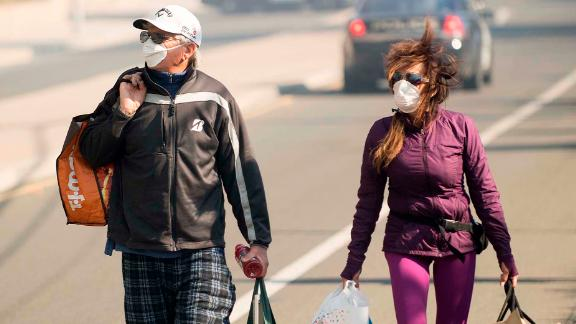 James and Josie Ralstin carry belongings retrieved from their home in Ventura on December 5.