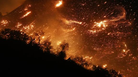 The Creek Fire burns on a hillside in the Shadow Hills neighborhood in Los Angeles. Strong Santa Ana winds are rapidly pushing multiple wildfires across the region.