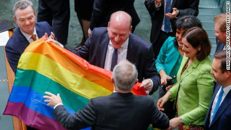 North Sydney federal Liberal MP Trent Zimmerman celebrates with the rainbow flag after parliament passed the same-sex marriage bill in the Federal Parliament in Canberra on December 7, 2017.  Gay couples will be able to legally marry in Australia after a same-sex marriage bill sailed through parliament on December 7, ending decades of political wrangling. / AFP PHOTO / SEAN DAVEY