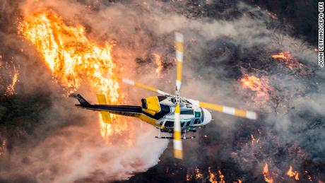 epaselect epa06372496 A Los Angeles County Fire helicopter flies over during the 'Skirball Fire' which began early morning in Bel-Air, California, USA, 06 December 2017. An outbreak of several fires North of Los Angeles has occurred as one of the strongest Santa Ana winds forecast of the season is ongoing and expected to last several days.  EPA-EFE/JOHN CETRINO