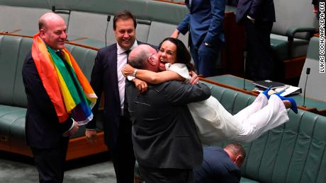 epa06373154 Liberal MP Warren Entsch (C-L) lifts up Labor MP Linda Burney (C-R) as they celebrate the passing of the Marriage Amendment Bill in the House of Representatives at Parliament House in Canberra, Australia, 07 December 2017. The passage of the bill effectively legalizes same-sex marriage in Australia.  EPA-EFE/LUKAS COCH  AUSTRALIA AND NEW ZEALAND OUT