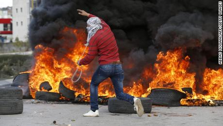 A Palestinian demonstrator runs past burning tires during clashes with Israeli troops during protests in the West Bank city of Ramallah on Thursday.