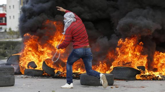 A Palestinian demonstrator runs past burning tires during clashes with Israeli troops during protests in the West Bank city of Ramallah on December 7