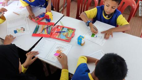 Younger students doing colouring work.