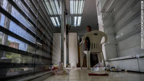 A security guard remains inside a looted pharmacy in Maracay, Aragua state, Venezuela on June 27, 2017. / AFP PHOTO / FEDERICO PARRA        (Photo credit should read FEDERICO PARRA/AFP/Getty Images)