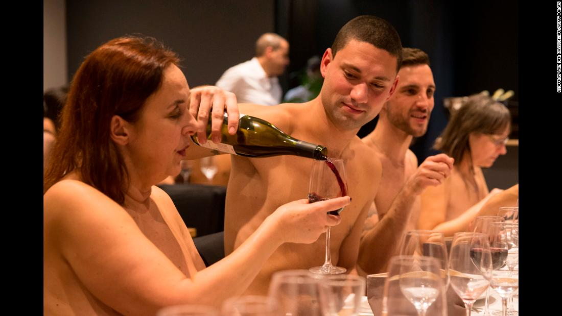 A man fills a wine glass for a woman at O'Naturel, a nudist restaurant in Paris, on Tuesday, December 5.