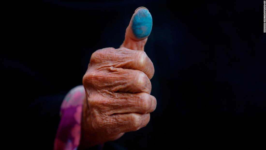 Asha Maya Dangol, 80, shows her thumbprint after voting in elections in Kathmandu, Nepal, on Thursday, December 7.