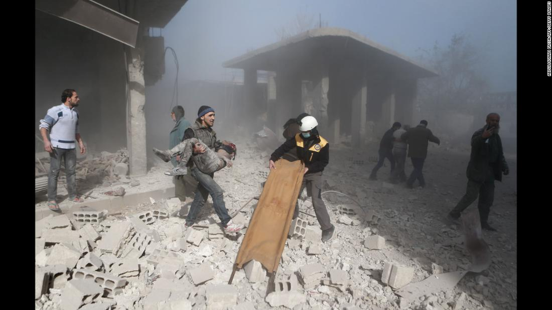 A man carries the body of a child who was killed in a reported airstrike in the rebel-held town of Hamouria, Syria, on Sunday, December 3.