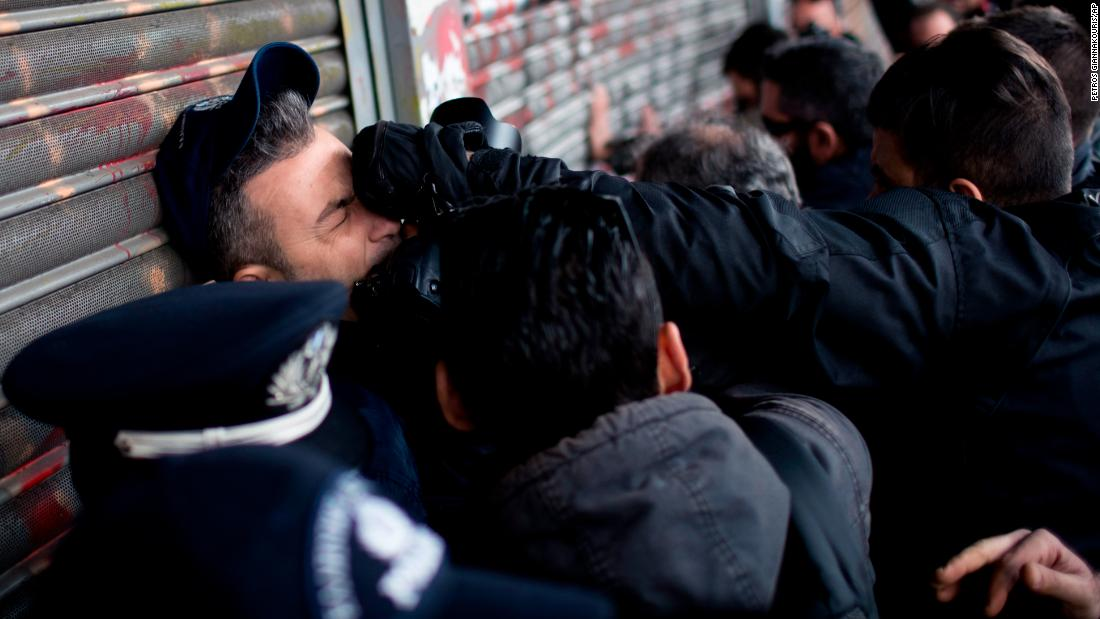 A police officer guarding the main entrance of the Labor Ministry is punched by a protester as communist-backed unionists tried to enter the building during a protest in Athens, Greece, on Tuesday, December 5. The protesters were demonstrating against proposals to amend a law regarding strikes.