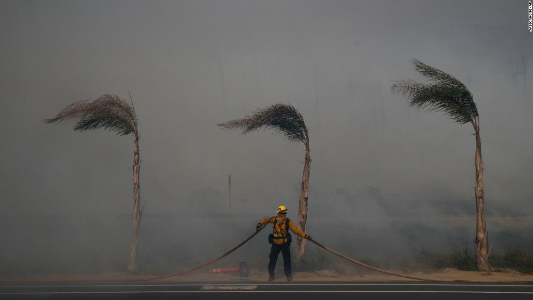 Palm trees sway in a gust of wind as a firefighter carries a hose in Ventura on December 7.