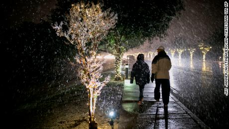 Larry and Licette Wagner walk in the snow on Escarpment Boulevard in Austin, Texas, on Thursday Dec. 7, 2017. (Jay Janner/Austin American-Statesman via AP)