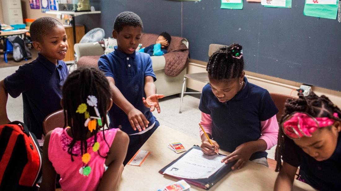 Future Ties mentors help the program participants with their homework. And sometimes the kids work in a game of Uno.