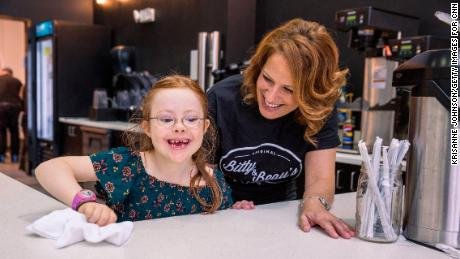 CNN Hero Amy Wright helps her daughter Bitty, 7, wipe down the counter at Bitty & Beau's Coffee in Wilmington, NC on Monday November 13, 2017. Bitty & Beau's Coffee is known as 'The Happiest Place in Wilmington', but that's not just because of its mochas and lattes -- at the heart of this North Carolina coffee shop's popularity is its unique staff.   Aside from the two store managers, everyone who works there has an intellectual or developmental disability (IDD), ranging from Down Syndrome to autism to cerebral palsy. CNN Heroes 2017 - Amy Wright Shoot ID, 27437_010