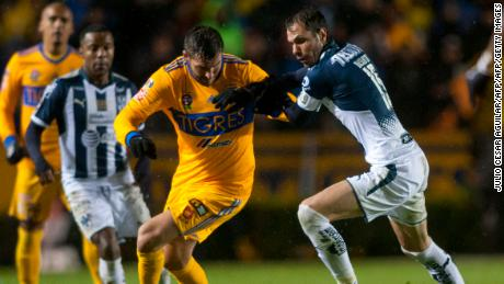 Andre Pierre Gignac (L) of Tigres  vies for the ball with Jose Basanta  (R) of Monterrey during the first leg of the final of Mexican Apertura 2017 tournament football match at the Universitario stadium in Monterrey, Mexico on December 7, 2017.  / AFP PHOTO / Julio Cesar AGUILAR