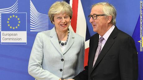 British Prime Minister Theresa May (L) is welcomed by European Commission Jean-Claude Juncker at European Commission in Brussels on December 8, 2017. / AFP PHOTO / EMMANUEL DUNAND