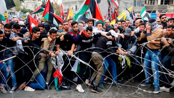 Protestors try to remove a  barbed wire fence outside of US embassy in Beirut.