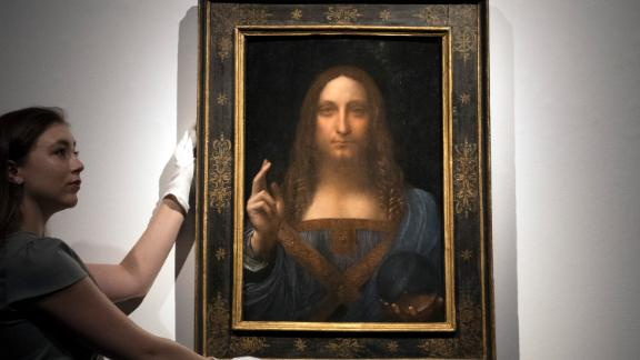 LONDON, ENGLAND - OCTOBER 24:  A member of staff poses with a painting by Leonardo da Vinci entitled