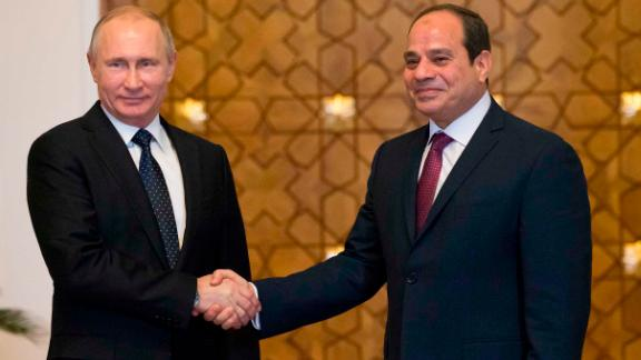 Putin (L) and Sisi shake hands during their meeting in Cairo on Monday.