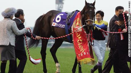 TOKYO, JAPAN - NOVEMBER 26: Jockey Yutaka Take who rode Deep Impact of Japan to victory in the 26th Japan Cup holds the horse at Tokyo Race Course on November 26, 2006 in Tokyo, Japan.  Britain's Ouija Board, ridden by Frankie Dettori came third . (Photo by Junko Kimura/Getty Images)