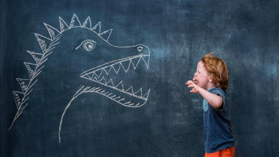 Young boy roaring at dinosaur drawing on blackboard