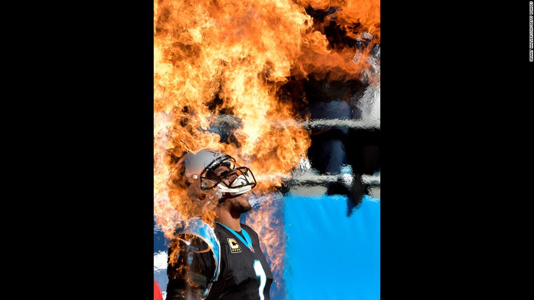 Carolina quarterback Cam Newton walks through pyrotechnics before an NFL game in Charlotte, North Carolina, on Sunday, December 10.