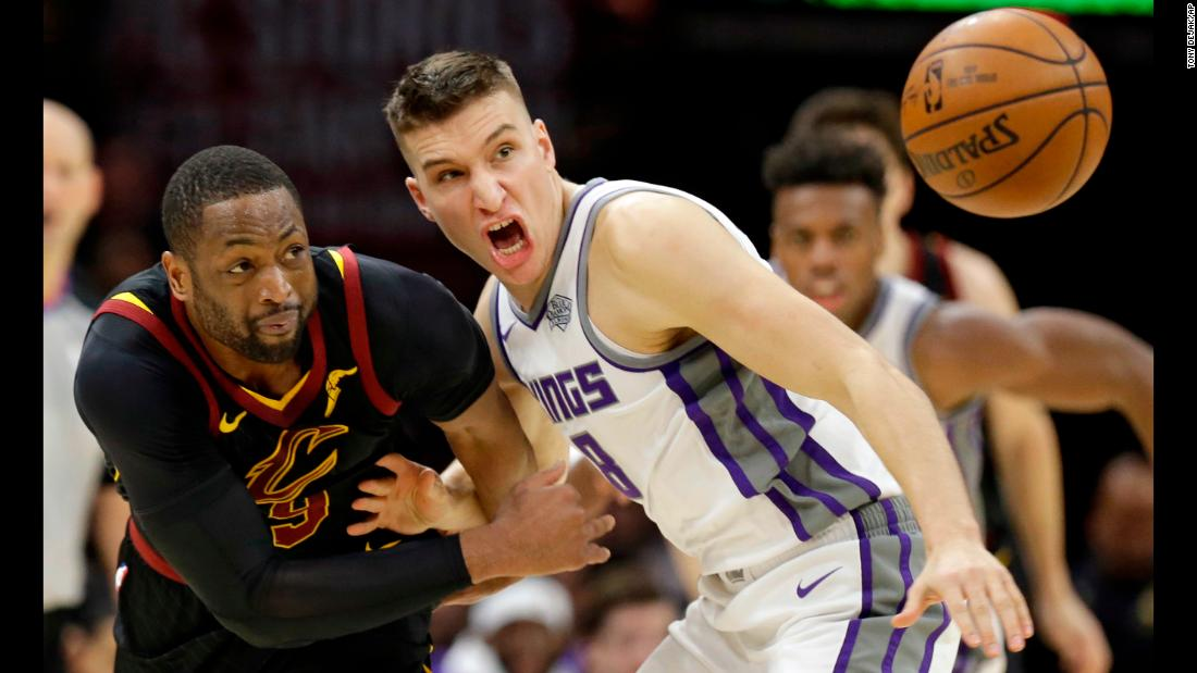 Cleveland's Dwyane Wade, left, and Sacramento's Bogdan Bogdanovic eye a loose ball during an NBA game in Cleveland on Wednesday, December 6.