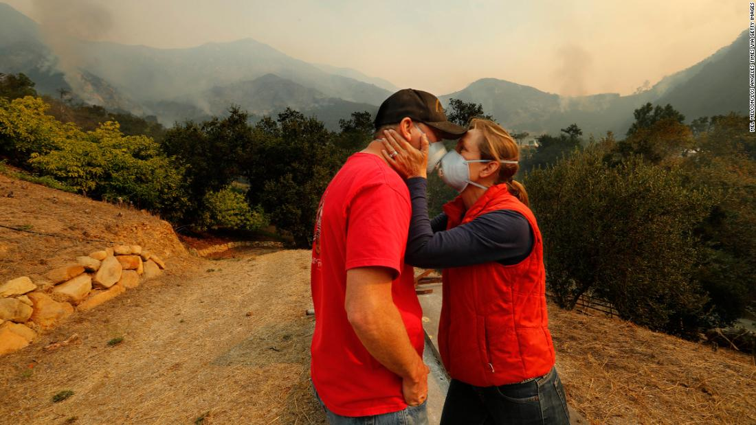 As the Thomas Fire burns in the background, Dan Bellaart and his wife, Mary McEwen, comfort each other in their backyard in Montecito, California, on December 11.