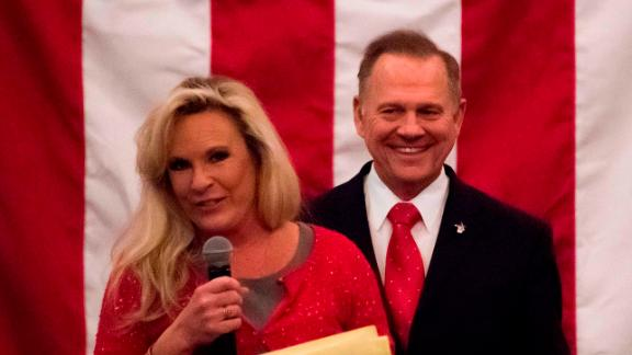 Republican Senatorial candidate Roy Moore smiles as his wife Kayla speaks at a rally in Midland, Alabama, on December 11, 2017. / AFP PHOTO / JIM WATSON        (Photo credit should read JIM WATSON/AFP/Getty Images)