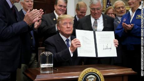 WASHINGTON, DC - DECEMBER 11:  (AFP OUT) U.S. President Donald Trump holds up 'Space Policy Directive 1' after signing it during a ceremony with NASA astronauts (R-L) Peggy Whitson, Buzz Aldrin and Jack Schmitt in the Roosevelt Room at the White House December 11, 2017 in Washington, DC. On the 45th anniversary of Apollo 17 -- the last crewed mission to the moon -- Trump signed the order directing NASA 'to lead an innovative space exploration program to send American astronauts back to the Moon, and eventually Mars,' according White House spokesman Hogan Gidley.  (Photo by Chip Somodevilla/Getty Images)