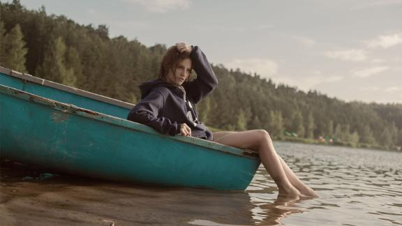 Stock image of a young woman in a boat by the river. Location unknown