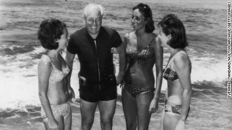 Australian prime minister Harold Holt on the beach with his three daughters-in-law, circa 1966.