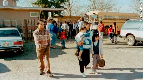 A couple leaves the Cleveland Elementary School in Stockton, California,  with their children after a gunman shot and killed five students and then turned the gun on himself.