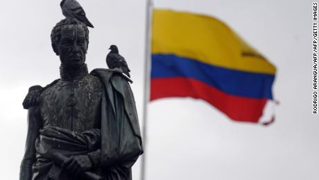 A Colombian flag wabes behind a staute of South American independece hero Simon Bolivar in Bogota on February 9, 2010. AFP PHOTO/Rodrigo ARANGUA / AFP PHOTO / RODRIGO ARANGUA        (Photo credit should read RODRIGO ARANGUA/AFP/Getty Images)