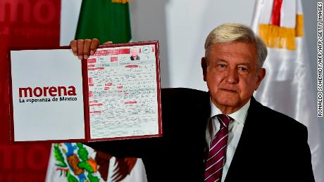 The president of the National Regeneration Movement (MORENA), Andres Manuel Lopez Obrador, shows the document after registering himself as a pre-candidate for Mexico's presidential election in July, in Mexico City, on December 12, 2017. / AFP PHOTO / Ronaldo SCHEMIDT        (Photo credit should read RONALDO SCHEMIDT/AFP/Getty Images)