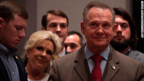 Republican Senatorial candidate Roy Moore (R) stands off stage with his wife Kayla (2nd L) before addressing his supporters in Montgomery, Alabama, on December 12, 2017. Democrat Doug Jones scored a victory Tuesday in a fiercely contested US Senate race in conservative Alabama, dealing a setback to US President Donald Trump, whose candidate could not overcome damaging sexual misconduct accusations. With 92 percent of precincts reporting, former prosecutor Jones secured 49.5 percent of the vote compared to Roy Moore's 48.8 percent, CNN and other networks reported.  / AFP PHOTO / JIM WATSON        (Photo credit should read JIM WATSON/AFP/Getty Images)