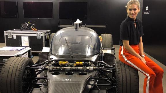 Nicki Shields poses with her rival, the AI race car DevBot at the Hong Kong ePrix earlier in December.